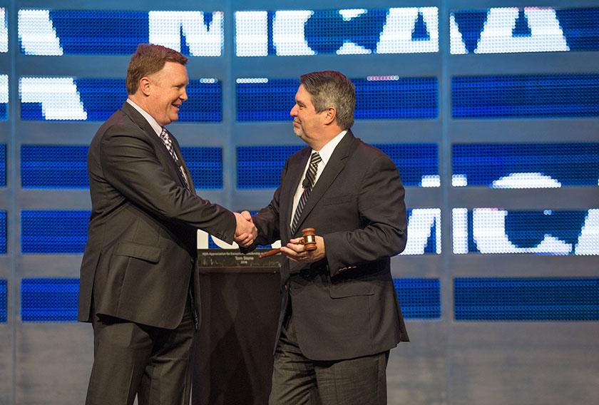 Tom Stone passes the MCAA Presidential gavel to Greg L. Fuller.