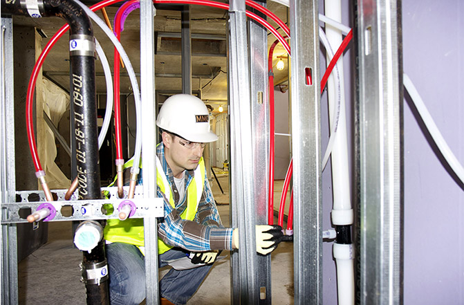 Chris Dent, MMC assistant project manager, examines the ProPEX expansion fitting connections in the Radisson Blu hotel.