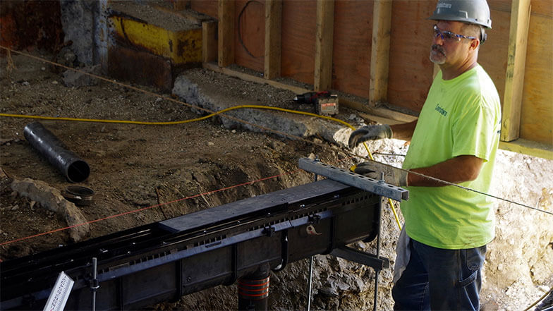 A worker begins installation of a Smith Enviro-Flo® II Trench Drain System
